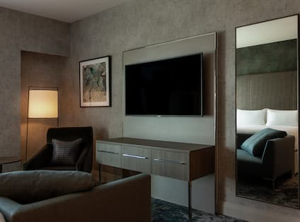 Suite with HDTV and Sofa and Reflection of Bed in Mirror