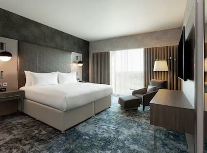 One King Bed Guestroom with Armchair and Footrest