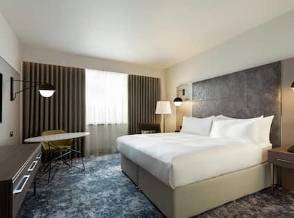 One Queen Bed Guest Bedroom with Armchair, Work Desk and TV