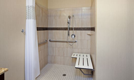 Accessible Guest Bathroom with Roll-In Shower, Bench and Handrails