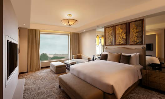 Presidential Suite With TV, Large Window With Open Drapes, Sofa, Ottoman, and Wall Art Above King Bed