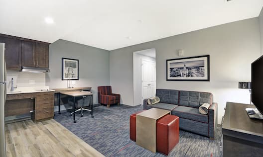 Suite Kitchen and Living Area with Lounge Seating, Work Desk, Television and Entry