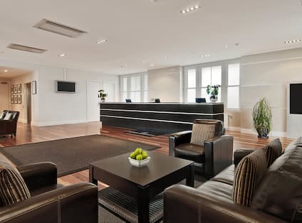 Lobby front desk seating area with sofas, soft chairs, and coffee tables