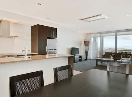 Suite apartment with kitchen, dining area with table and chairs, living room with sofa, chairs, coffee table, TV, and floor-to-ceiling windows with outdoor view