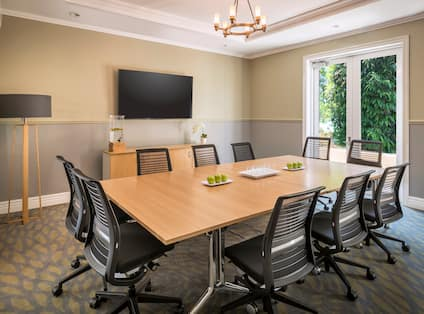 Boardroom Meeting Table with Office Chairs and Wall Mounted HDTV