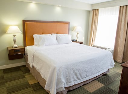 One King Bed with Bedside Lamps in Suite Bedroom