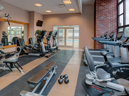 Fitness center with cardio machines and bench