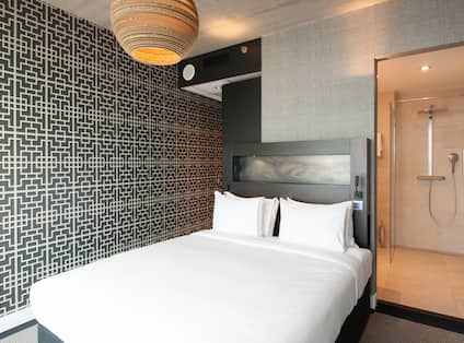 Bed in Hotel Guest Room and View of Shower in Bathroom