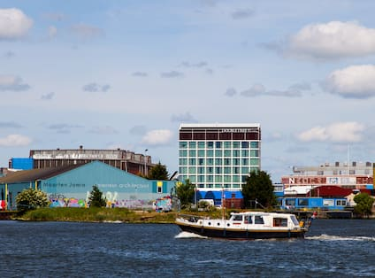 Daytime View of Boat in Body of Water With Hotel in the Background