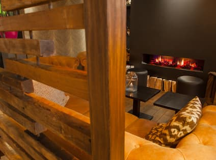 Soft Seating, Tables and Fireplace Behind Wooden Wall Partition