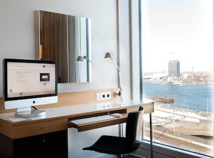 a work desk with a computer monitor and a view of the water
