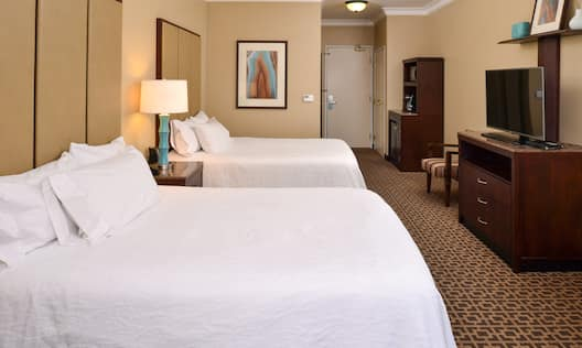 Double queen room with beds and TV.