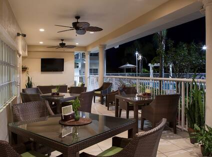 Outside Dining on Illuminated Restaurant Porch With TV and Ceiling Fans at Night