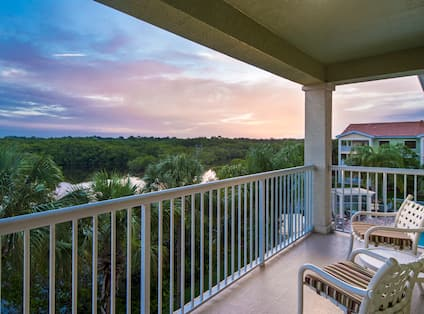 Two Chairs on Guest Room Balcony With View of River at Sunset