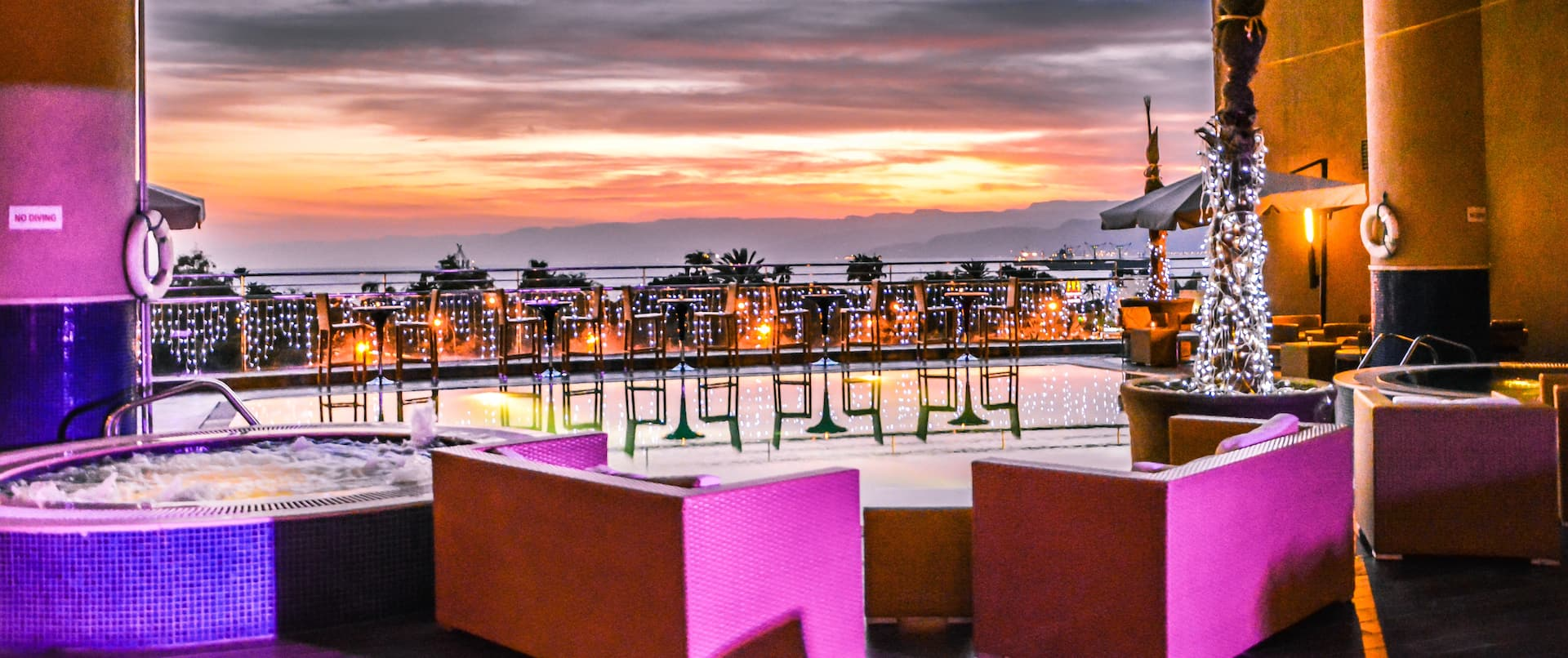 Infinity Chill Out Area With Lounge Seating by Hot Tub Illuminated in Pink Lights at Sunset
