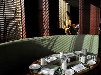 Detailed View of Place Settings on Oval Table by Window and Green Booth and Two Brown Chairs in Gusto Resaturant