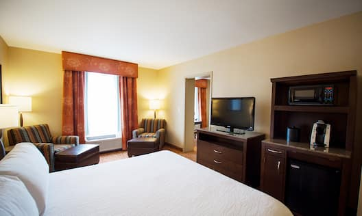 King hearing accessible  room with bed, TV, refreshment area, and armchairs.