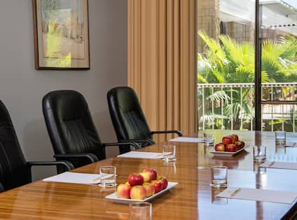 Three Black Chairs at Boardroom Table by Window With Outside View