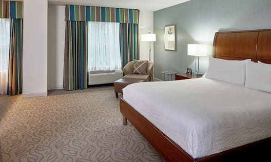 King-Size Bed, Lounge Chair, and Ottoman in Mobility Accessible Guest Room