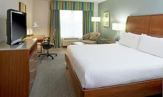 King-Size Bed, Work Desk with Ergonomic Chair, Flat Screen TV, and Lounge Chair in Guest Room