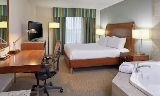 King Bed, Whirlpool Bathtub, Work Desk with Ergonomic Chair, and Flat Screen TV in Guest Room