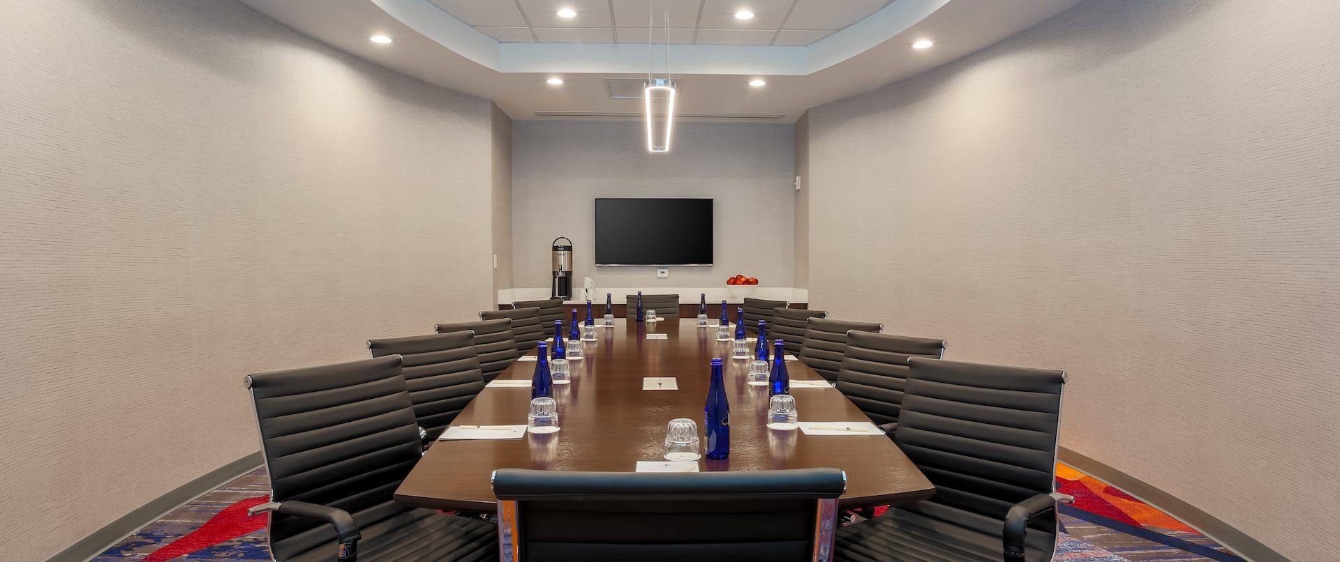 TV and Boardroom Table Surrounded by Black Chairs in Meeting Space