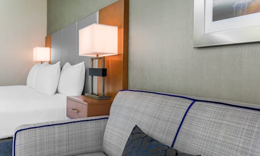 Bed With Illuminated Lamps on Bedside Tables, and Wall Art Above Sofa