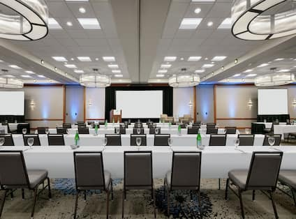 Spacious ballroom facility equipped with classroom style tables, projector screens, podium, and stage.