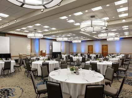 Spacious ballroom facility equipped with round tables with beautiful place settings, project screens, and stage.