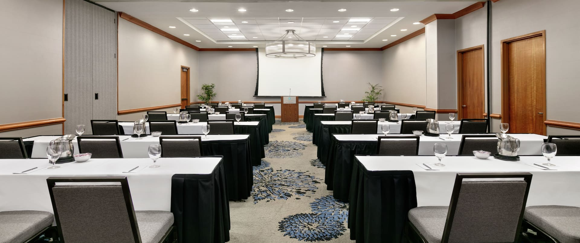 Spacious meeting room facility equipped with classroom style tables, projector screen with equipment, and podium.