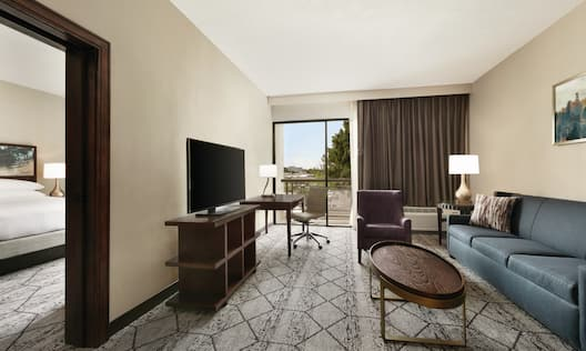 Accessible Suite Living Area with Bed, Lounge Area, Outside View, Work Desk, and Room Technology