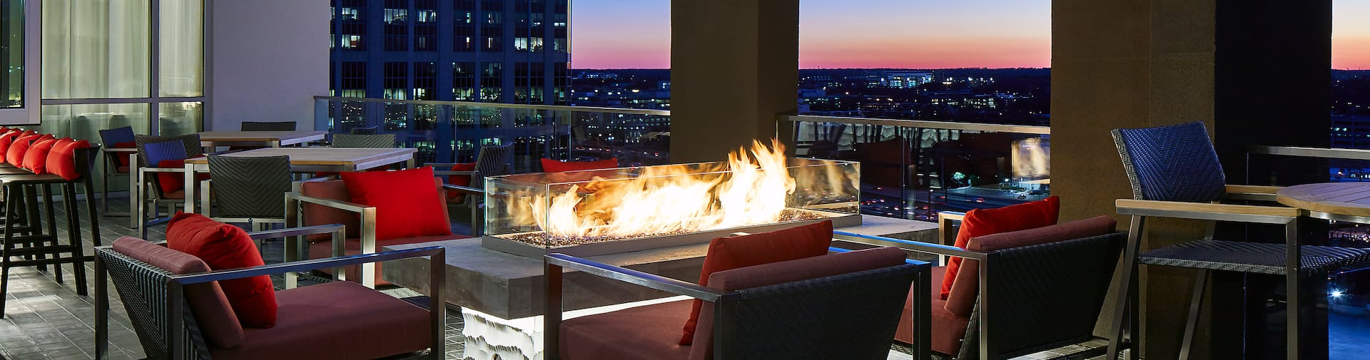 a fire pit and seating on a terrace with skyline views