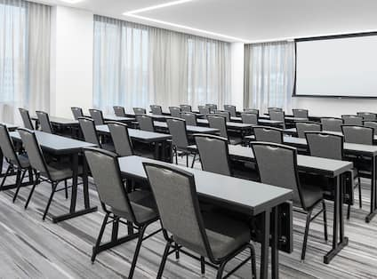 Meeting Room Set Up Classroom Style with Tables, Chairs, and Projector Screen