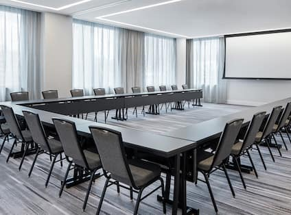 Meeting Space with U-Shaped Table Setup with Chairs and Projector Screen