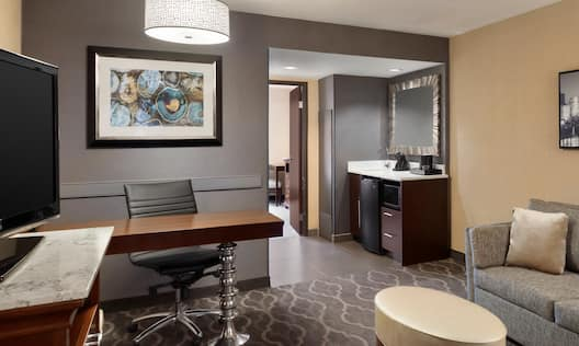 Guest Suite Lounge Area with HDTV, Work Desk, Footrest, Sofa and Beverage Station