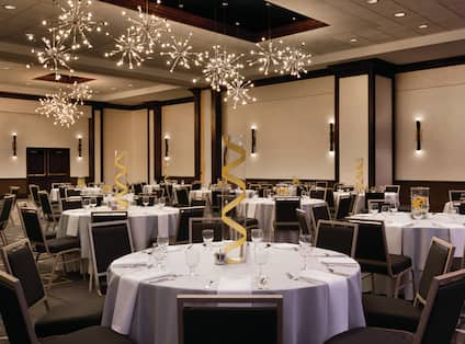 Meeting room in ballroom setup with round tables with place settings