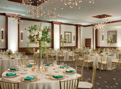 Room set up for a wedding dinner with gold seats and gold decorations