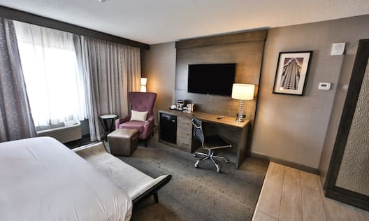 Oversized King Bed, Armchair in Corner by Window, TV Above Work Desk With Illuminated Lamp, and Wall Art