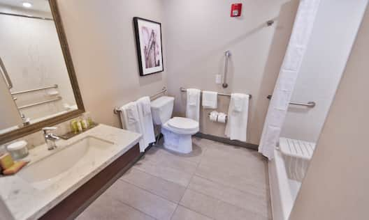 Large Vanity Mirror, Sink, Fresh Towels, Toiletries, Wall Art Above Toilet With Grab Bars, Accessible Bathtub With Shower Seat and Grab Bars