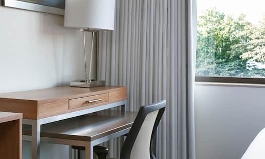 King Bed Facing Wall Art Above Work Desk With Lamp and Ergonomic Chair by Large Window With Open Drapes