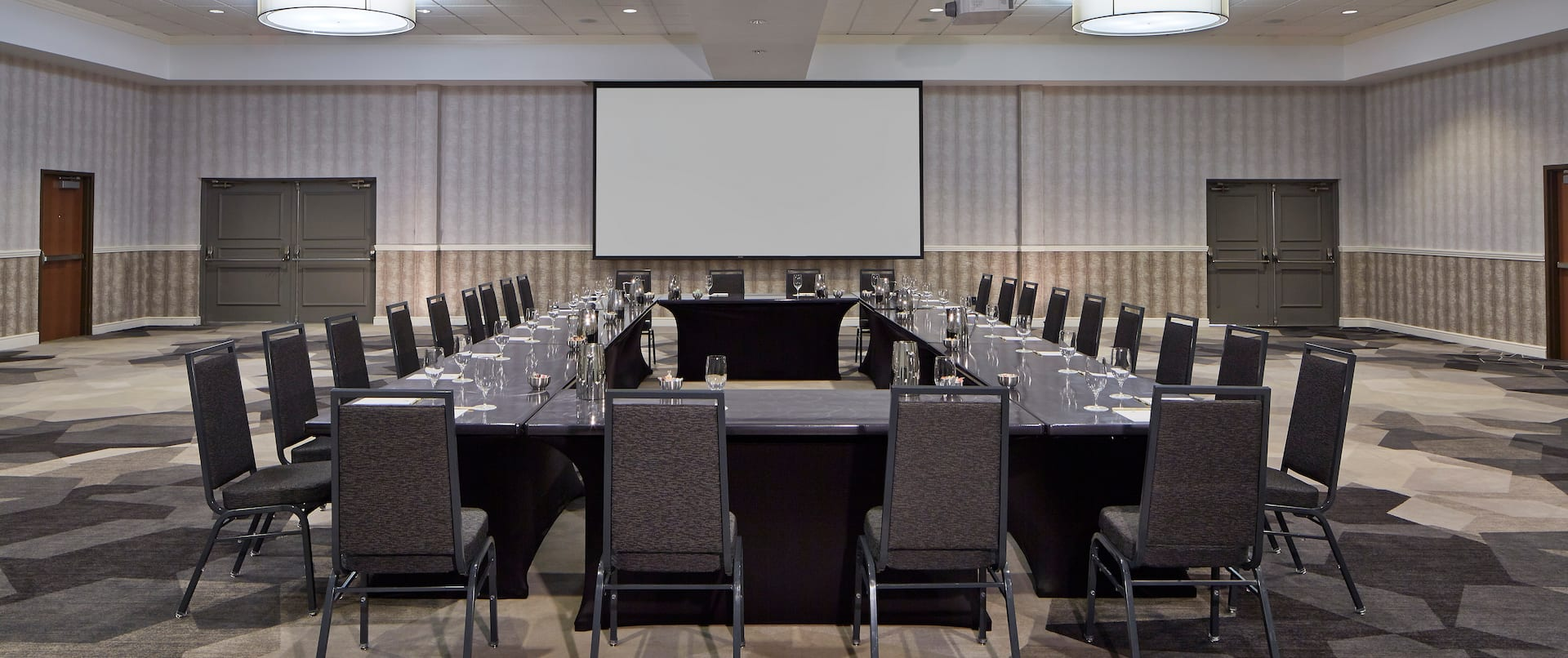 Meeting Room With Projector Above Hollow Square Table With Black Chairs and Projector Screen