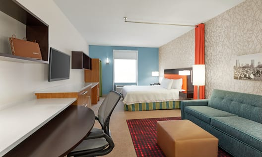 Bright studio suite featuring work desk with ergonomic chair, living area with pullout sofa bed, and king bed with privacy curtain.