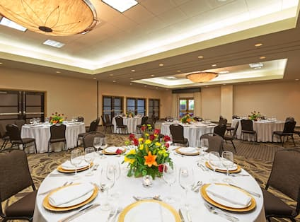 Round Tables in Ballroom With Place Settings, Flowers and Candles on White Tablecloths