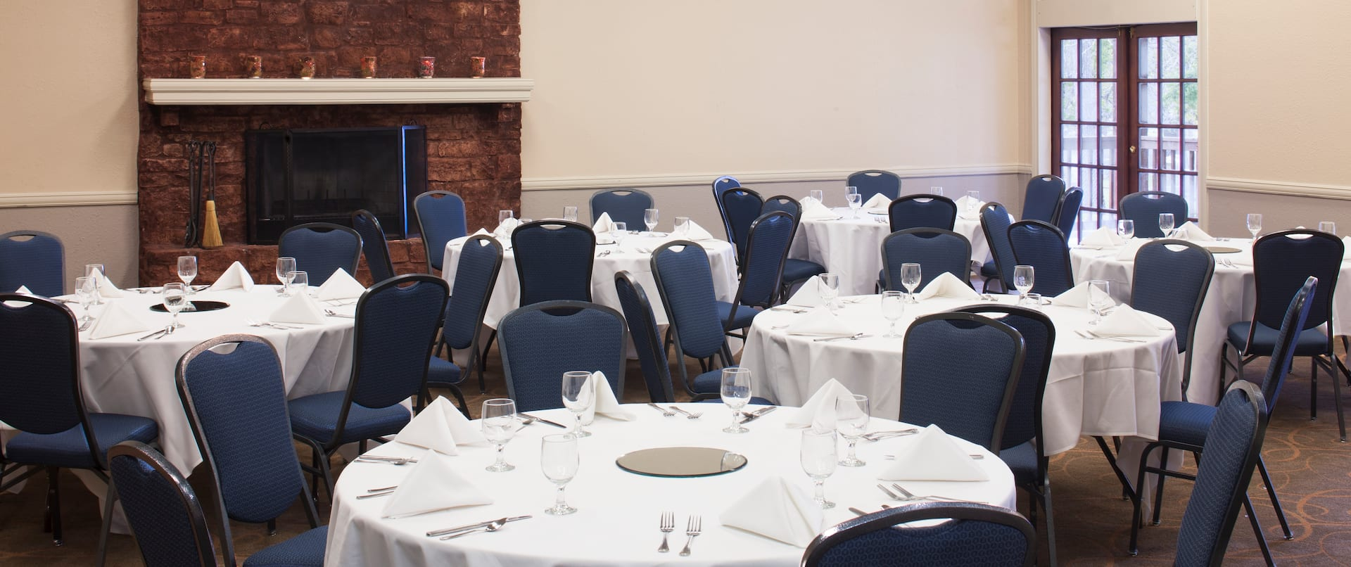 Place Settings on Round Tables With White Tablecloths, Blue Chairs, Wall Art Above Fireplace, and Window in University Meeting Room