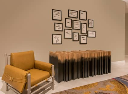 Detailed View of Wall Art Above Wooden Art Feature and Armchair in Pre-Function Lounge Area