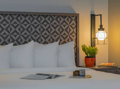 Detailed View of Magazine on Neatly Made Bed, Headboard With Geometric Designs, Illuminated Lamp Above Bedside Table With Plant and Books