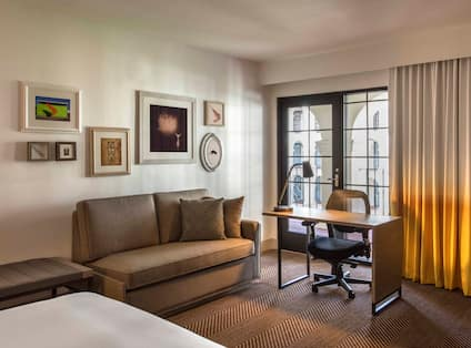 Bed, Wall Art Above Sofa, Illuminated Lamp on Work Desk By Balcony Door With Courtyard View