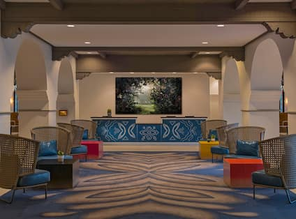 """View of Tables, Lounge Seating and """"Prelude"""" Wall Art by Ysabel Lemay Behind Front Desk"""