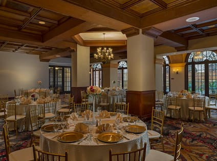 Dovers Meeting Room With Flowers, Place Settings and Gold Plates on Round Tables With Cream Colored Tablecloths