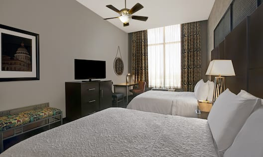 guest room with beds television and windows